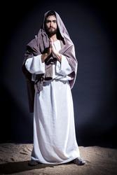 Jesus Christ praying to God  in the dark blue night