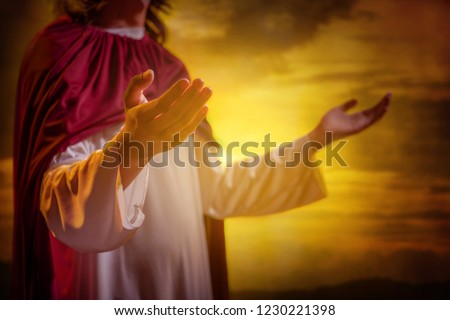 Jesus christ raising hands and praying with sunset background