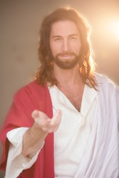 Jesus Christ smiling and offering his hand in blessing backlit in radiant light