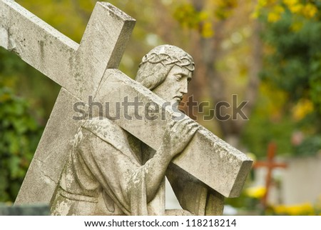 Jesus Christ statue in a cemetery at fall