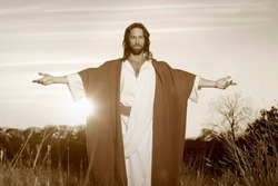Jesus Christ with outstretched arms in welcoming blessing bathed in the light of God