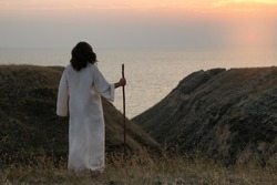 Jesus Christ with stick on hills at sunset, back view. Space for text