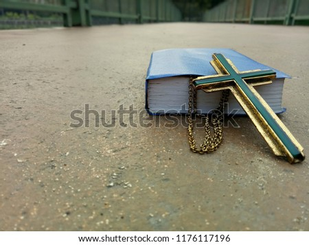 Jesus christian cross necklace and blue covered book of bible on ground, God loving concept picture with selective focus
