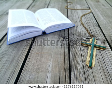 Jesus christian cross necklace and blue covered book of bible page opening on wooden panel ground, God loving concept picture with selective focus and copy space