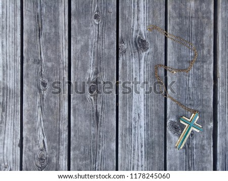 Jesus christian cross necklace on right side of wooden panel floor background, God loving concept picture with selective focus and copy space