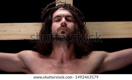Jesus closed eyes on cross dark background, forgiveness of sins, religious love