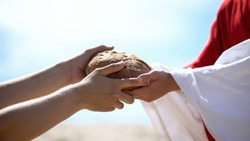Jesus hands giving bread to poor man, biblical story to feed hungry, charity