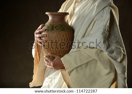 Jesus Holding a jug of water on a dark background