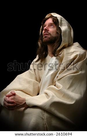 Jesus in prayer over a dark background - stock photo