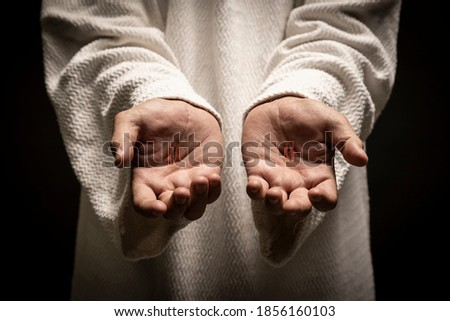 Jesus of Nazareth showing the wounds on his hands while praying on a dark night after being resurrected. Foto stock ©