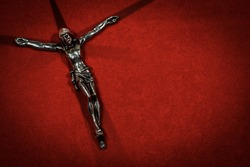 Jesus on the Cross. Closeup of a silver crucifix with cross made of shadows on a red velvet background with copy space.