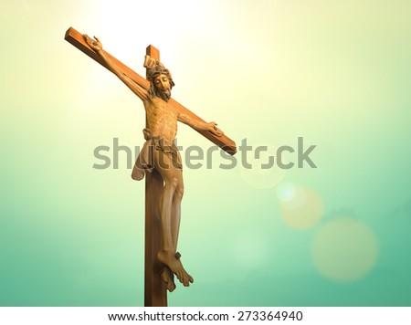 Jesus on the cross over blue sky background. (Public wooden Jesus on the cross)