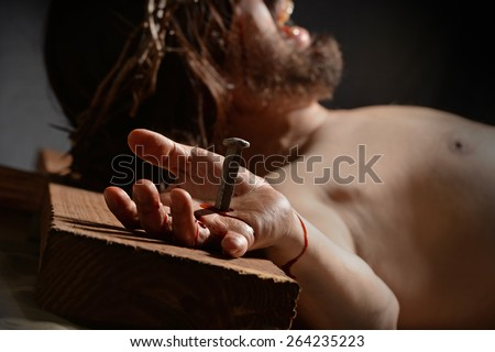 Jesus  on the cross with nail and hand in foreground