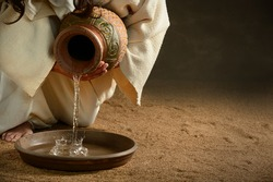 Jesus pouring water from jug over dark background