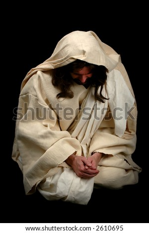 Jesus praying on his knees over a black background