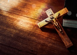 Jesus's crucifix over bible on wooden table background,Christian world mission concept,  copy space