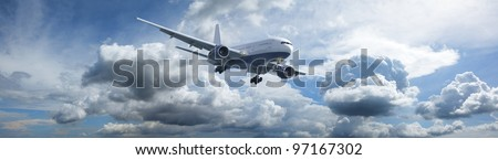 Jet aircraft in a blue cloudy sky is maneuvering for landing. Panoramic composition in high resolution.