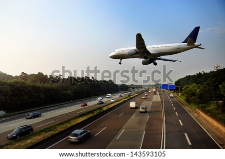 Shutterstock Jet aircraft on landing approach flying low over dual carriageway