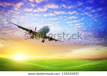 Jet aircraft over the field of green at sunset