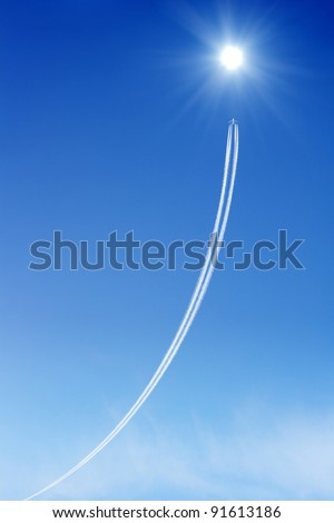 Jet aircraft rises to the bright sun in blue sky. Way to success. Concept of progress, improvement. - stock photo