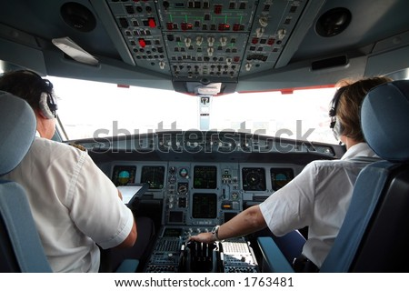 Jet airplane cockpit with two pilots crewmembers - stock photo