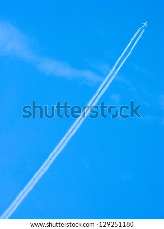 Jet airplane soars into the blue sky leaving contrails in its wake - stock photo
