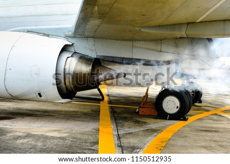 Jet engine of aircraft (airplane) blowing white smoke while engine running first time after maintenance. Jet engine of aircraft(airplane) running at idle speed for leak check and maintenance.