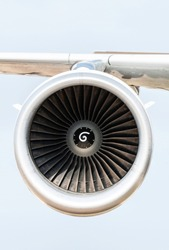 Jet engine on the airplane wing. Close-up frontal view of the jet engine and sky on the background. Air transport conception.