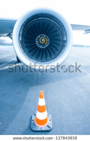 Jet engine with traffic cone in front, blue light