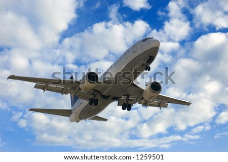 Jet landing (Boeing 737) over a cloudy sky background