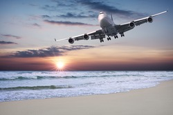 Jet liner is flying over the beach at sunset