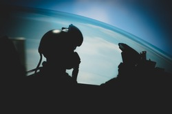 Jet pilot , The military pilot in the plane in a helmet in dark blue overalls against the blue sky