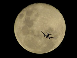 jet plane flying over the full moon that has a golden hue during a clear and dark night, Brazil
