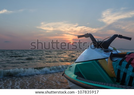 Jet ski parked on a beach against blue sky and sunset