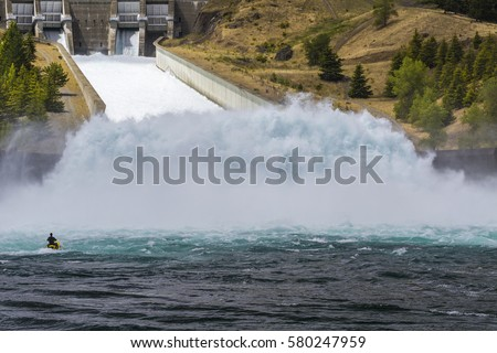 Jet skier facing a wall of water from the spillway at Benmore Hydro Electric Dam, in Waitai District, South Island, New Zealand