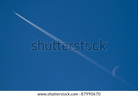 jet stream of airplane going through the moon in blue sky