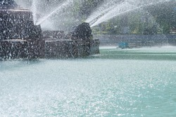 Jets and drops of water from the fountain in the blue water pool in the park