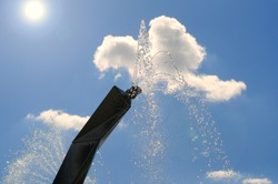Jets and splashes of water from the fountain against the background of blue sky and summer sun