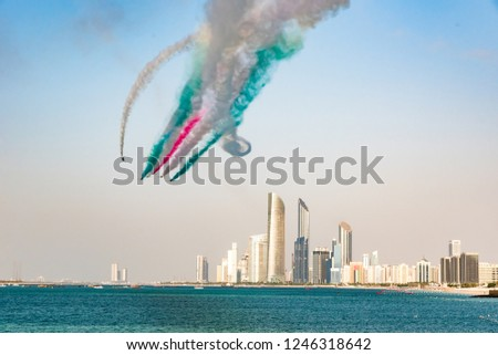 Jets soaring the skies of u.a.e. on National day leaving behind trails of colorful smoke over city and it's Corniche/breakwater area. Aerobatics against the city scape of Abu Dhabi during air show.