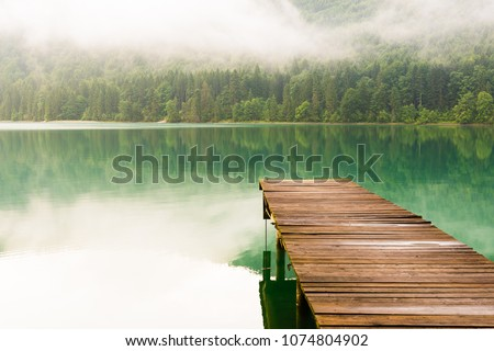 Jetty at lake Walchensee in the Alps of Bavaria on a misty morning in summer