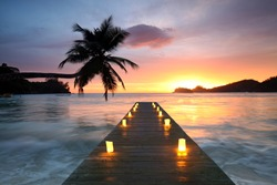 Jetty beach at sunset with candles, romantic seychelles holiday