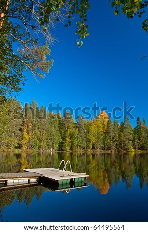 Jetty from sauna to lake with beutiful colors on autumn and reflection of trees in Finland.