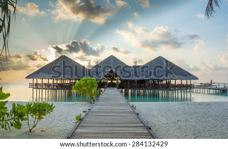 Jetty leading to overwater resort hotel restaurant and arrival