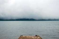 Jetty on a foggy mountain lake Beratan in Bali. Calm water under dense clouds