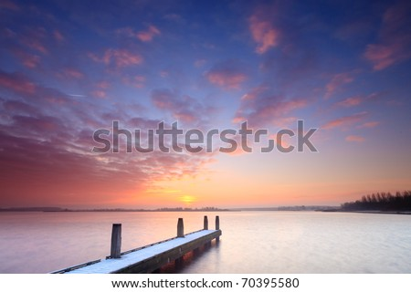 Jetty on lake at sunset