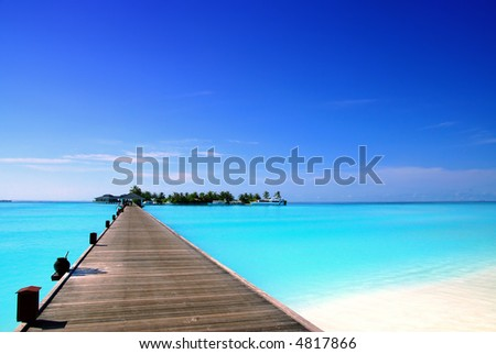 jetty that leads to an tropical island on the maldives