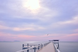 Jetty to the clear blue-violet path calm sea, with flying birds and mountains as background.Jetty to the clear blue-violet path, calm sea, with flying birds and mountains as background.With copy space