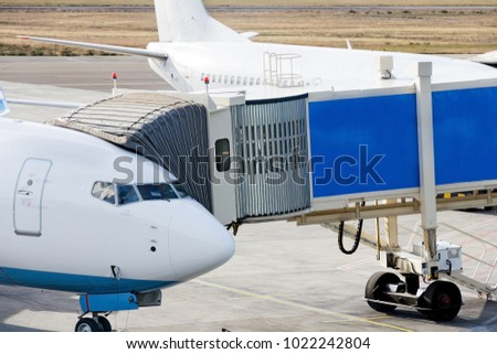 Jetway is served to passenger airplane at airport. Close up. Preparation for departure, boarding passengers on board.