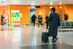 Jew orthodox with a suitcase is going around the airport