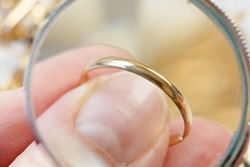 jeweler looking at beautiful golden wedding ring, jewerly inspect and verify, pawnshop concept, jewerly shop concept